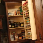 A traditional door spice rack  offers convenient kitchen storage in a wall cabinet.