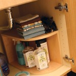 A two-tiered shelf provides extra storage on either side of the plumbing fixtures.