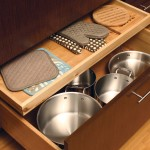 Conveniently store oven mitts and potholders in a shallow roll-out above a pot and pan drawer.