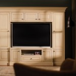 """The entertainment cabinetry is designed to perfectly fit this large screen TV.  Designer Cabinetry shown with """" Chapel Hill Classic"""" door style, Beaded Inset, in Maple with Vanilla/Espresso Glaze finish."""